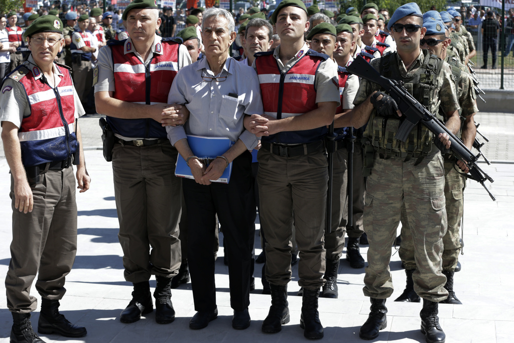Paramilitary police and members of the special forces escort former Air Force commander Akin Ozturk and other suspects of last year's failed coup, out...