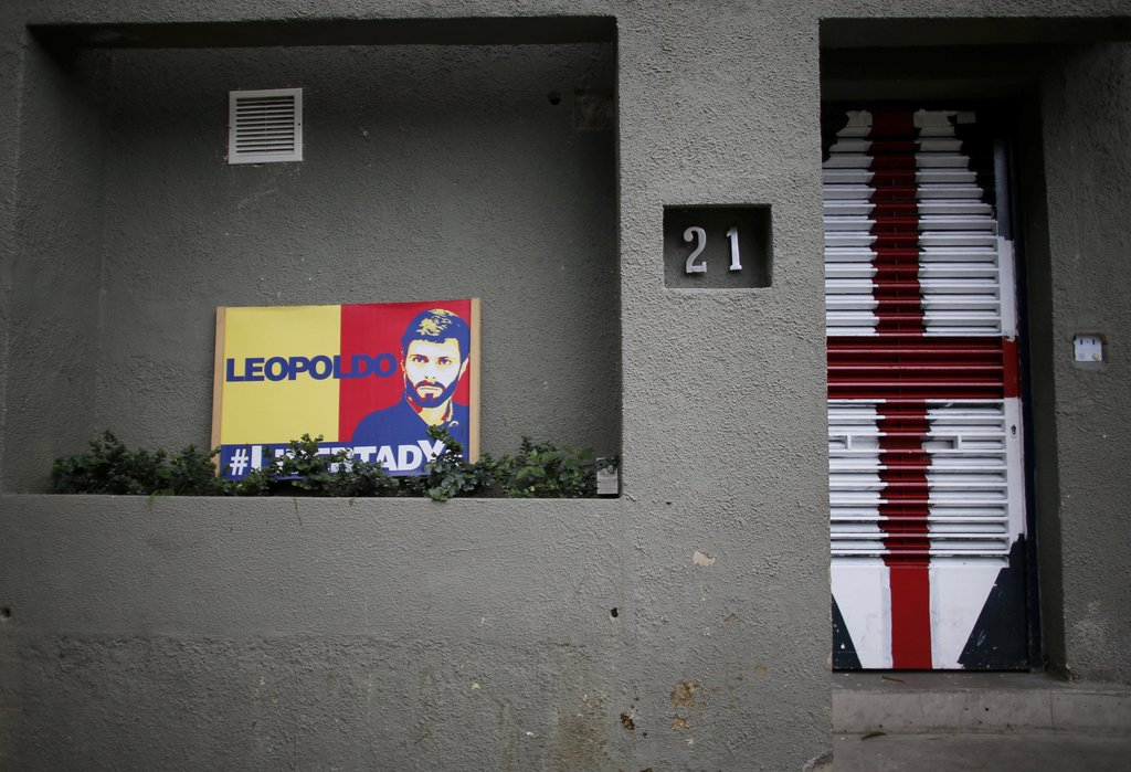 In this Tuesday, Aug. 1, 2017 photo, a sign with an image of jailed opposition leader Leopoldo Lopez sits outside his home in Caracas, Venezuela. Late...
