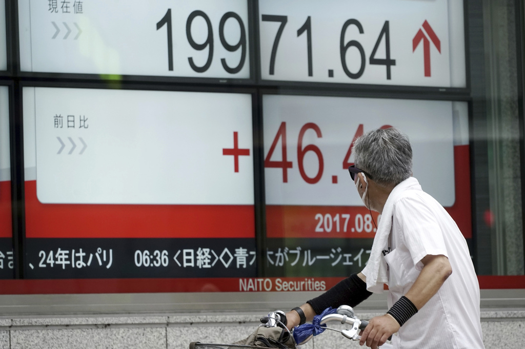 A man looks at an electronic stock board showing Japan's Nikkei 225 index at a securities firm in Tokyo, Tuesday, Aug. 1, 2017. Asian stock markets ad...