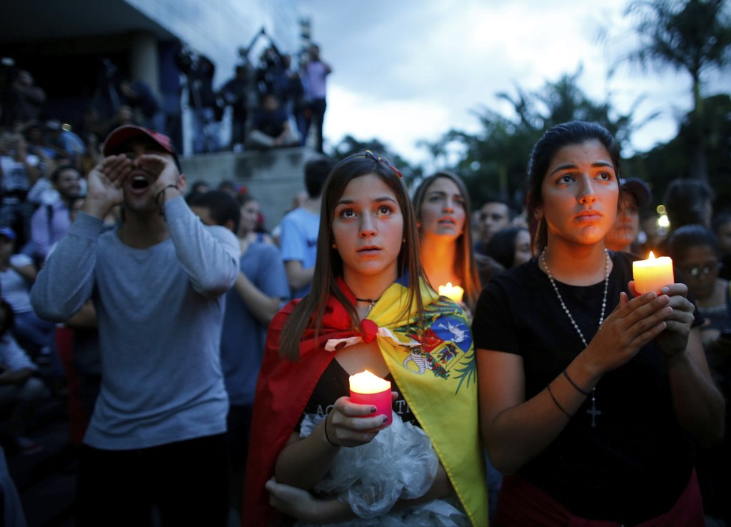 In this Monday, July 31, 2017 photo, anti-government demonstrators attend a candle light vigil in honor of those who have been killed during clashes b...
