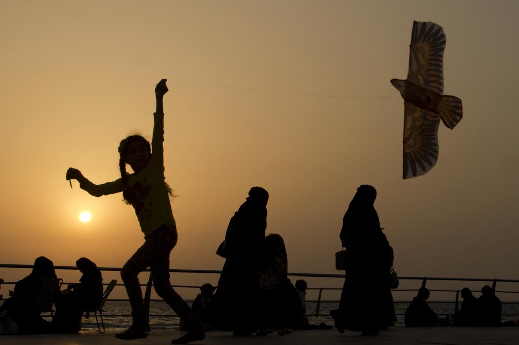 FILE- In this Saturday, April 8, 2017 file photo, a girl plays with her kite as visitors walk on the Red Sea beach, in Jiddah, Saudi Arabia. Saudi Ara...