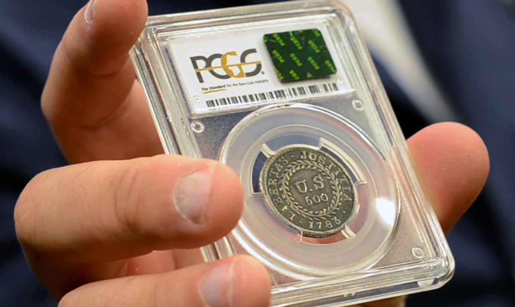 In this Monday, July 31, 2017, image made from a video, David McCarthy, a senior numismatist at Kagin's, holds what is believed to be the first coin e...
