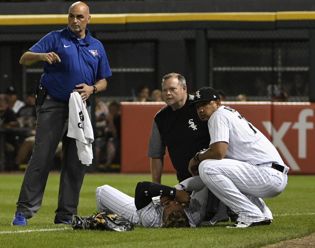 Chicago White Sox second baseman Yoan Moncada, bottom, lies on the field after colliding with right fielder Willy Garcia (61) on a double hit by Toron...