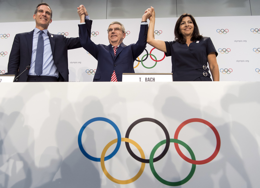 FILE - Int his July 11, 2017, file photo, from left, Mayor of Los Angeles Eric Garcetti, International Olympic Committee (IOC) President Thomas Bach, ...
