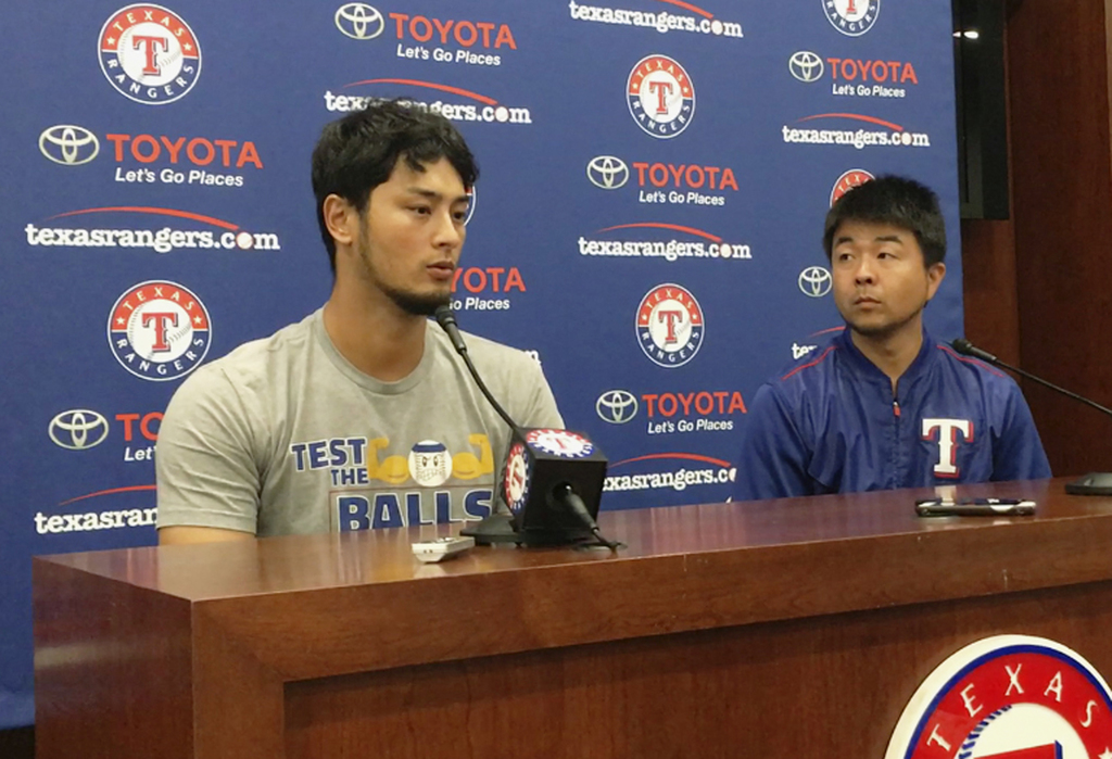 Former Texas Rangers pitcher Yu Darvish, left, responds to a question during a news conference as his translator Hideaki Sato prepares to translate re...
