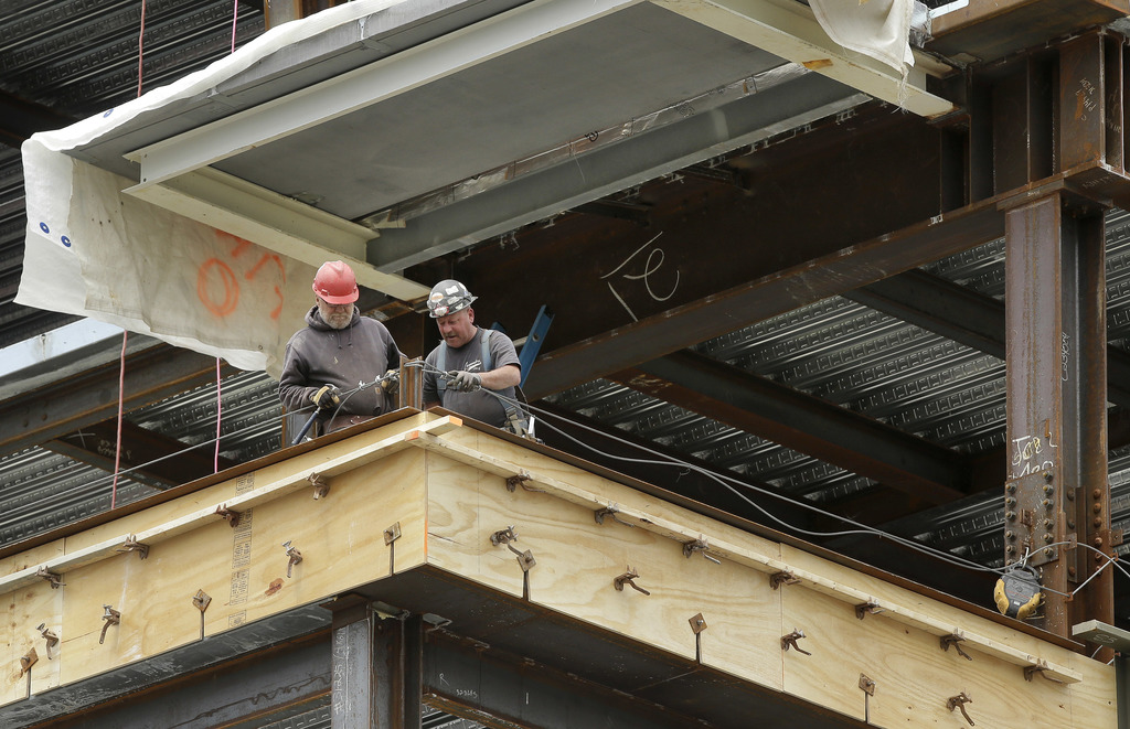 In this Thursday, May 19, 2016, photo, workers construct a high-rise building in Boston. On Tuesday, Aug. 1, 2017, the Commerce Department reports on ...