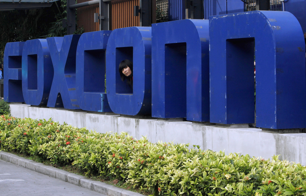 FILE - In this May 27, 2010 file photo, a worker looks out through the logo at the entrance of the Foxconn complex in the southern Chinese city of She...