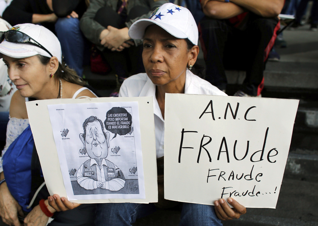 """An anti-government demonstrator holds a sign that reads in Spanish """"Constituent Assembly fraud!"""" during a vigil in honor of those who have been killed..."""