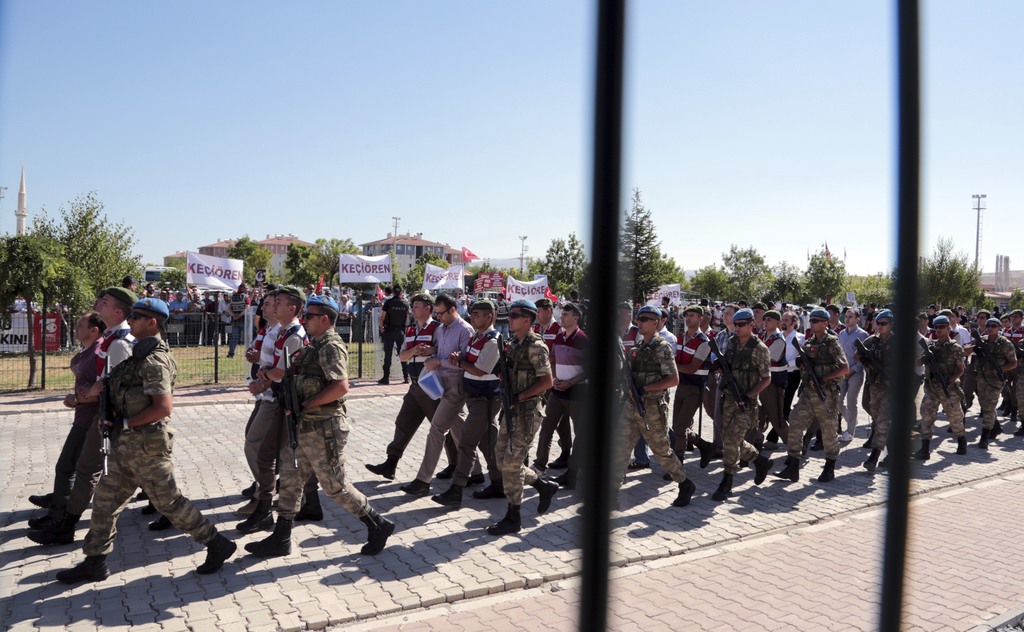 Paramilitary police and special force members escort outside the courthouse as the trial of 486 suspects, including a number of generals and F-16 pilo...