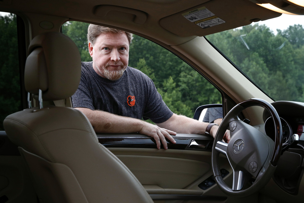 In this July 28, 2017, photo, John Carroll poses alongside his 2010 Mercedes-Benz ML 350 sport utility vehicle, which contains a driver's side Takata ...