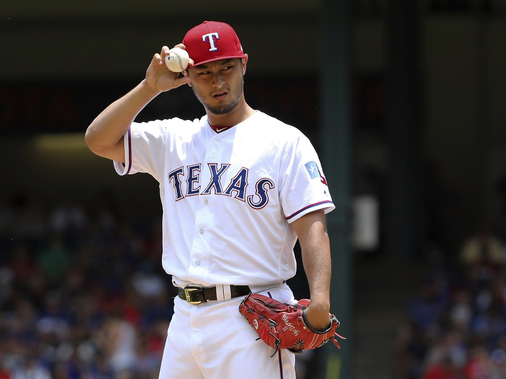 FILE - In this July 9, 2017, file photo, Texas Rangers starting pitcher Yu Darvish adjusts his hat as he works the first inning of a baseball game aga...