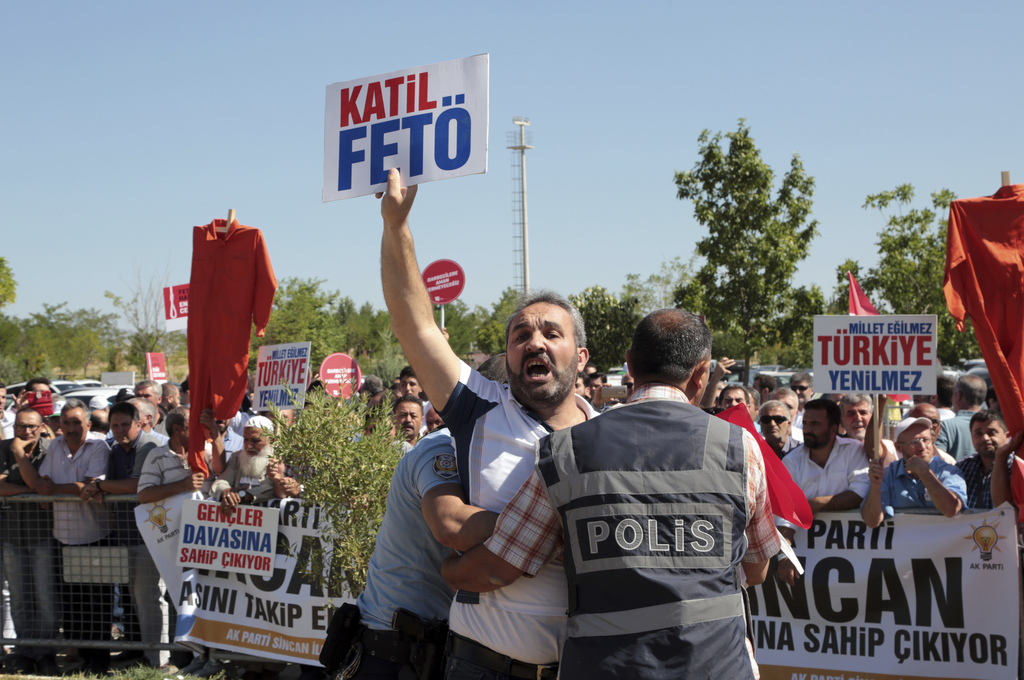 """A man waves a placard that reads """" Assassin Fethullahist Terrorist Organisation """" as paramilitary police and special force members escort outside the ..."""