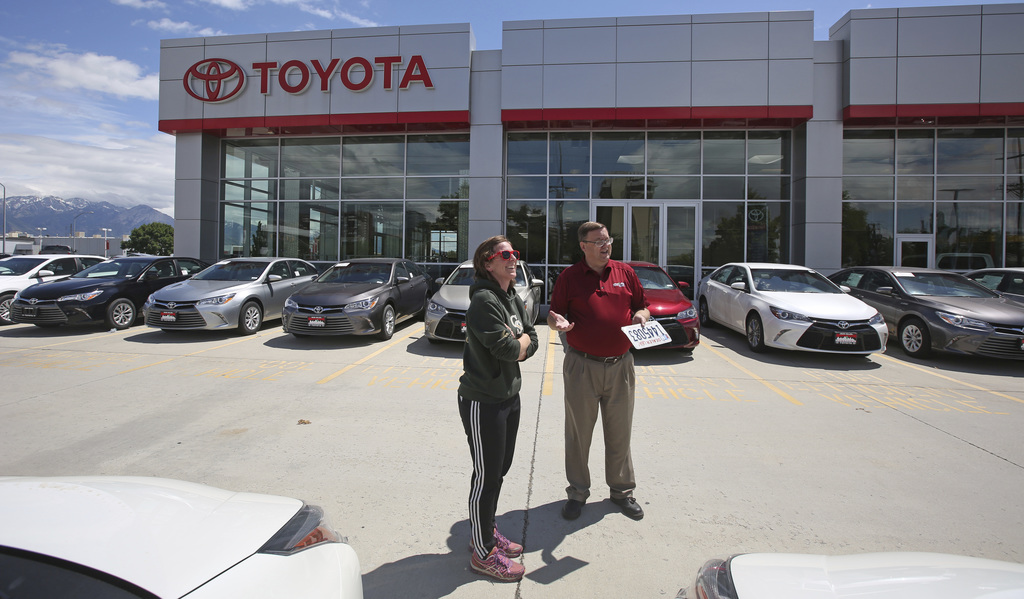In this Tuesday, June 13, 2017, photo, car shopper Mary Jean Jones speaks with Mark Miller Toyota salesman Doug Lund, in Salt Lake City. U.S. sales of...