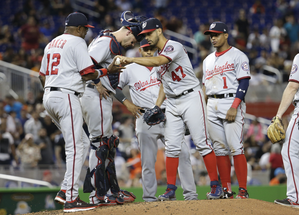 Washington Nationals starting pitcher Gio Gonzalez (47) gives the ball to manager Dusty Baker (12) after being relieved during the ninth inning of a b...