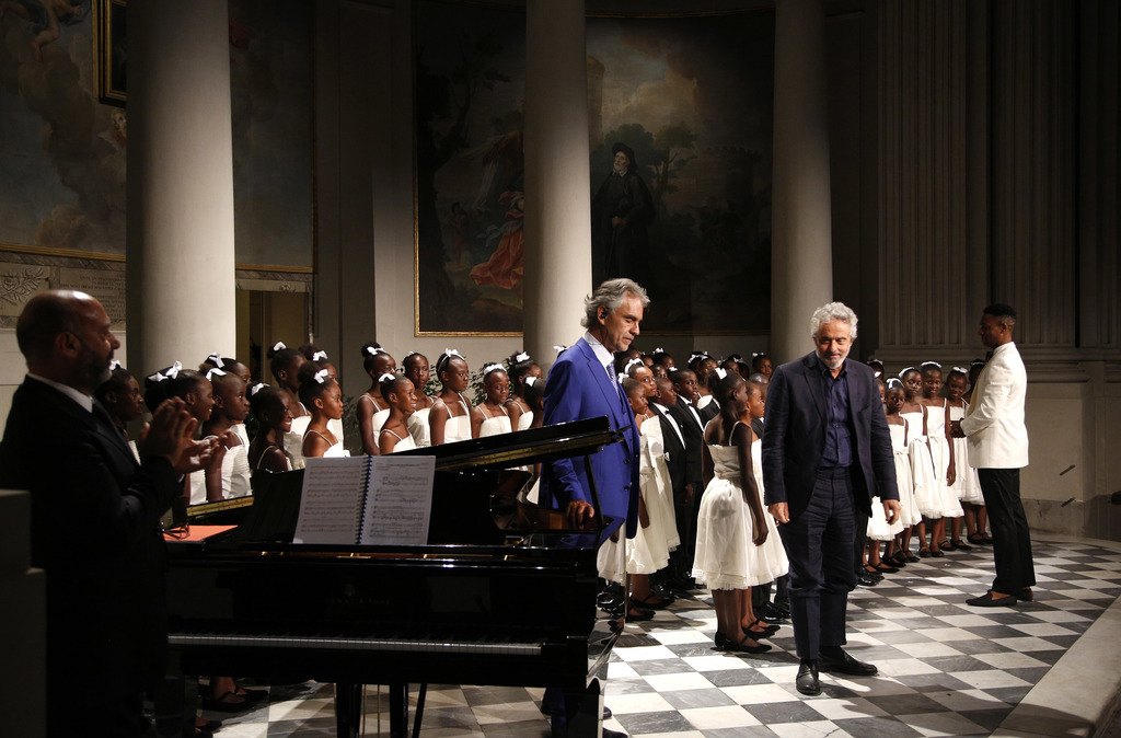"""Tenor Andrea Bocelli, center left, and composer Nicola Piovani, center right, acknowledge applause as they perform with the """"Voices of Haiti"""" children..."""