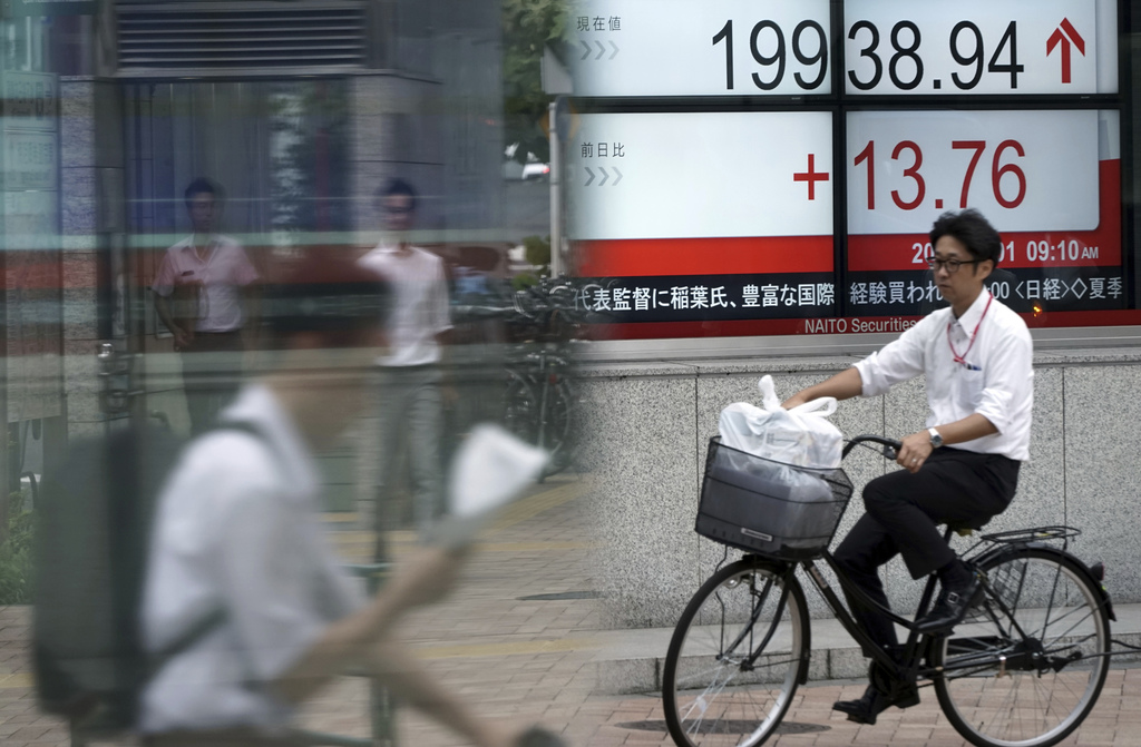 People commute past an electronic stock board showing Japan's Nikkei 225 index at a securities firm in Tokyo Tuesday, Aug. 1, 2017. Asian stock market...