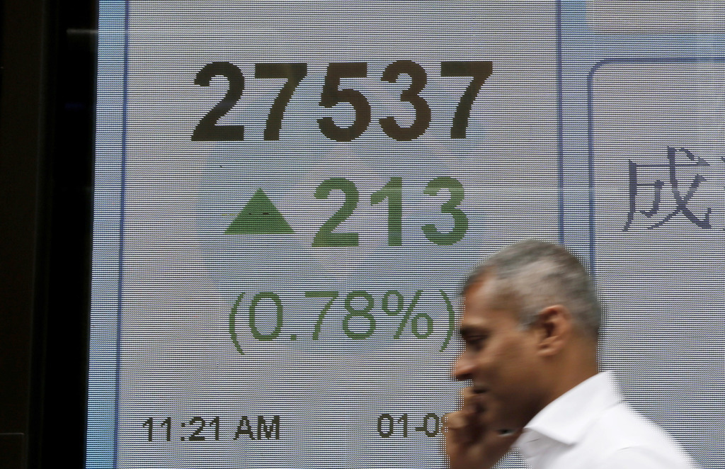 A man walks past an electronic stock board showing the Hang Seng Index at a bank in Hong Kong, Tuesday, Aug. 1, 2017. Asian stock markets advanced Tue...