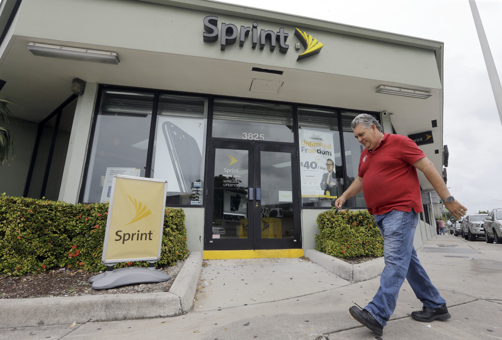 FILE - In this Friday, Oct. 28, 2016, file photo, a person walks by a Sprint store in Miami. On Tuesday, Aug. 1, 2017, Sprint Corp. reported fiscal fi...