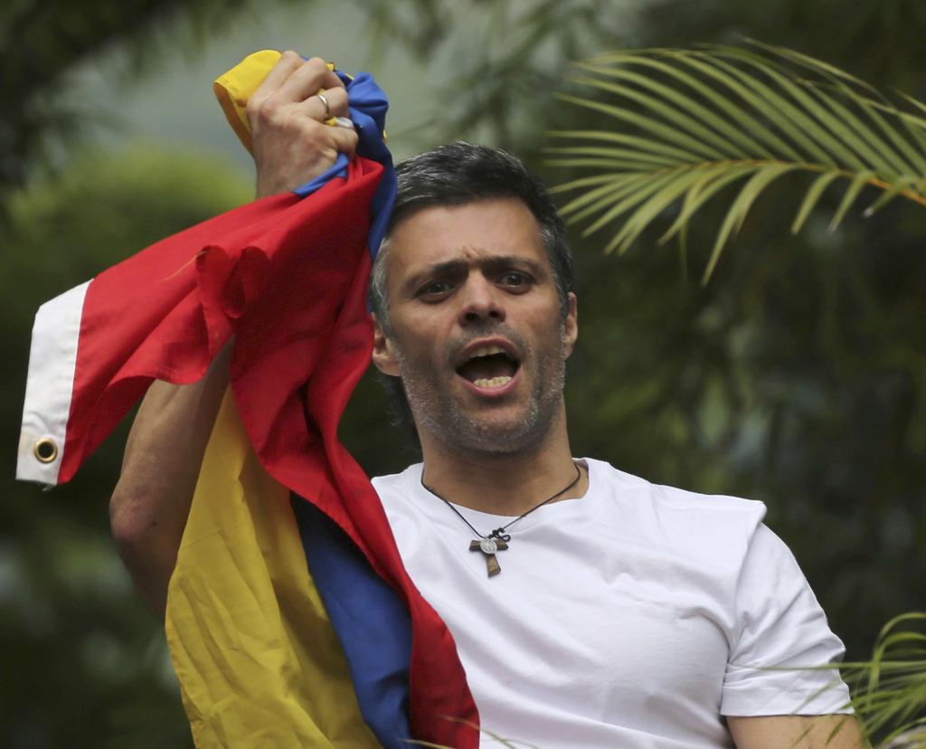 FILE - In this Saturday, July 8, 2017, file photo, Venezuela's opposition leader Leopoldo Lopez holds a national flag as he greets supporters outside ...