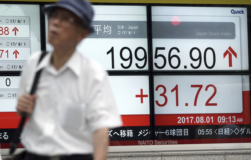 A man walks past an electronic stock board showing Japan's Nikkei 225 index at a securities firm in Tokyo Tuesday, Aug. 1, 2017. Asian stock markets a...