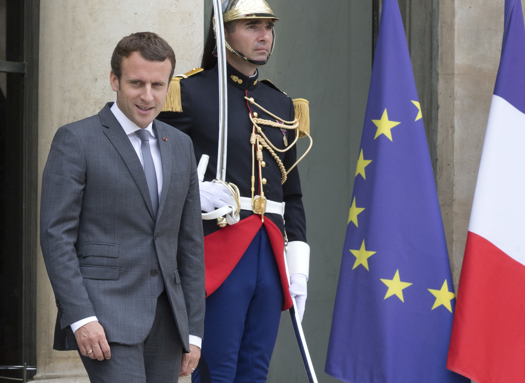FILE - In this Monday, July 31, 2017 file photo file French President Emmanuel Macron walk out of the Elysee Palace in Paris, France. France's lower h...