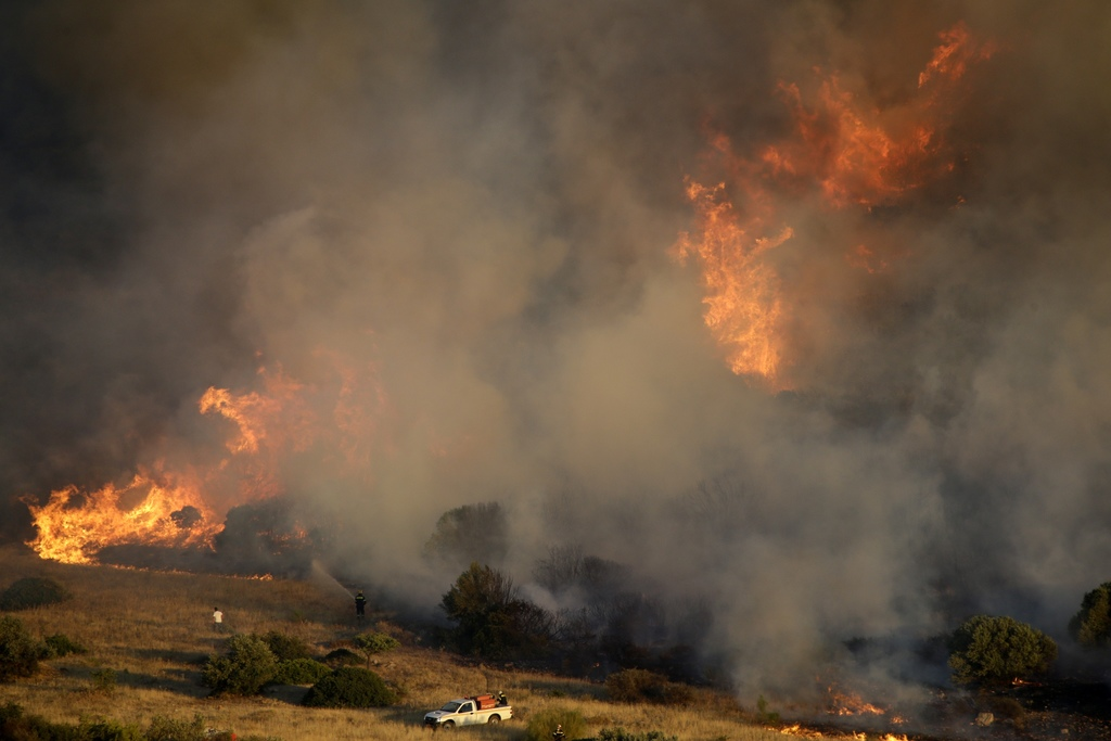 Firefighters try to extinguish a fire in the Kalyvia area some 30 kilometers (18 miles) south of Athens, Monday, July 31, 2017. Dozens of firefighters...