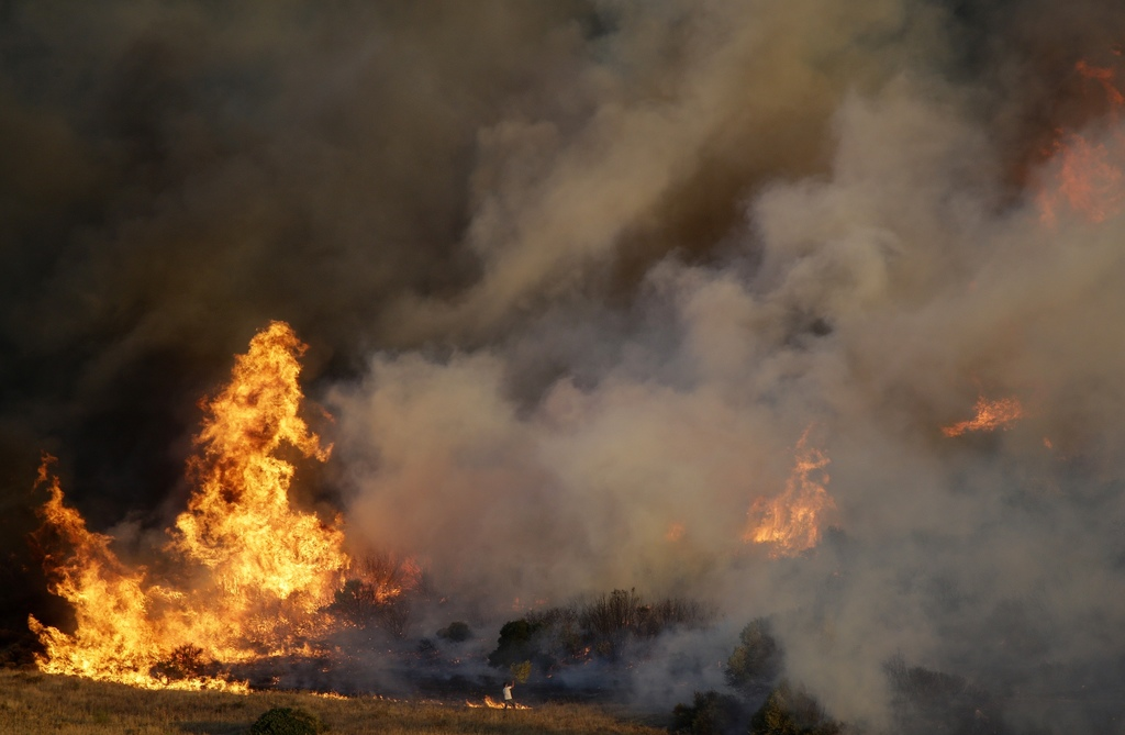 A local resident tries to extinguish a fire in the Kalyvia area some 30 kilometers (18 miles) south of Athens, Monday, July 31, 2017. Dozens of firefi...