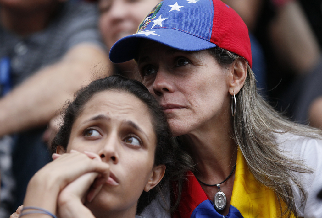 Anti-government demonstrators attend a vigil in honor of those who have been killed during clashes between security forces and demonstrators in Caraca...