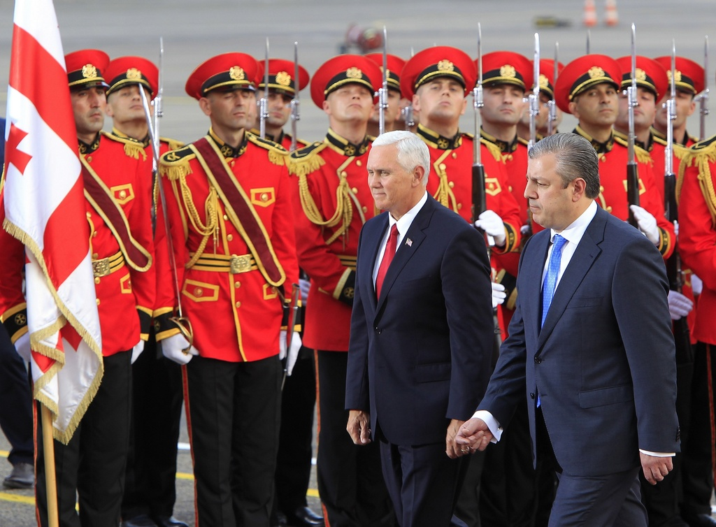 U.S. Vice President Mike Pence, left, and Georgian Prime Minister Giorgi Kvirikashvili attend a welcome ceremony at the airport outside Tbilisi, Georg...