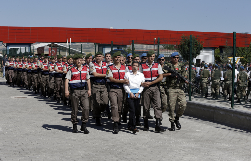 Paramilitary police and members of the special forces escort unidentified suspects of last year's failed coup, outside the courthouse at the start of ...