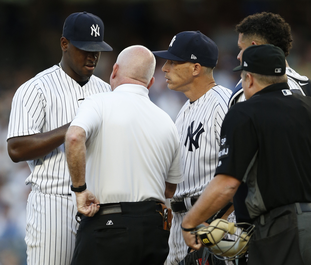 New York Yankees trainer Steve Dohonue, second from left, and manager Joe Giradi, third from left, check on New York Yankees starting pitcher Luis Sev...