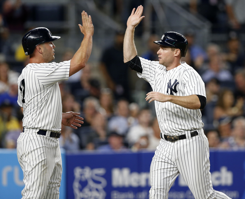 New York Yankees designated hitter Matt Holliday, left, greets Chase Headley after they scored on Todd Frazier's two-run single during the fourth inni...