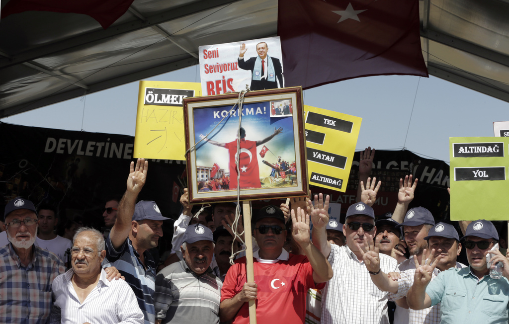 Supporters of President Recep Tayyip Erdogan demonstrate as paramilitary police and members of the special forces escort suspects of last year's faile...