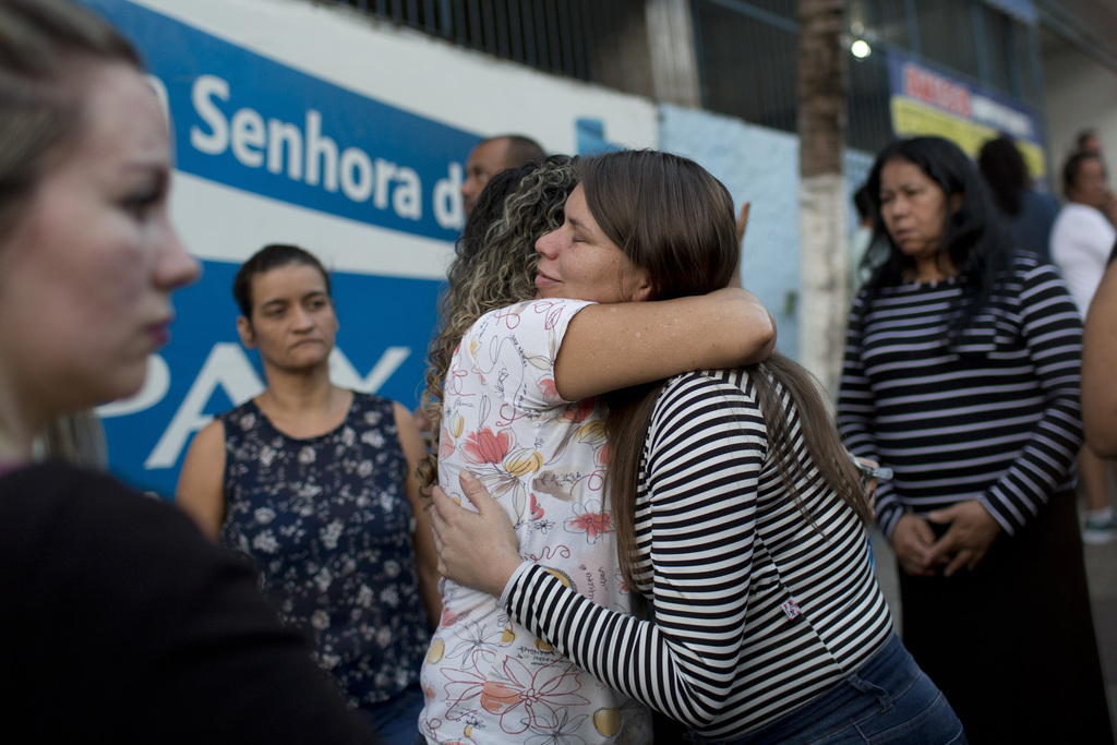Claudineia dos Santos Melo, right, is comforted during the burial of her son Arthur, at a cemetery in Rio de Janeiro, Brazil, Monday, July 31, 2017. T...