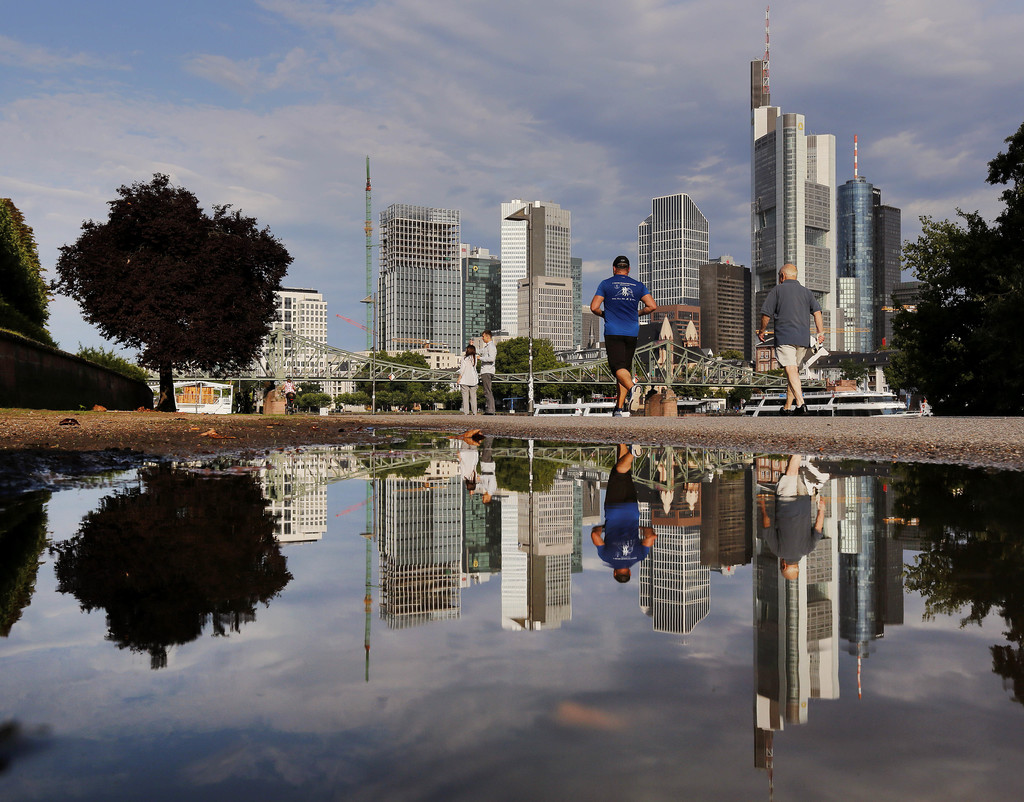 The skyline of the banking district is reflected in a puddle after a heavy thunderstorm during the night in Frankfurt, Germany, Tuesday, Aug. 1, 2017....