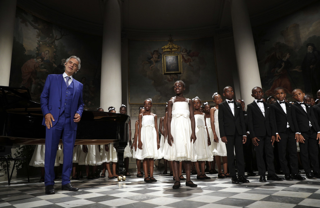 """Tenor Andrea Bocelli, acknowledges applause as he performs with the """"Voices of Haiti"""" children's choir during the concert that inaugurates the Franco ..."""