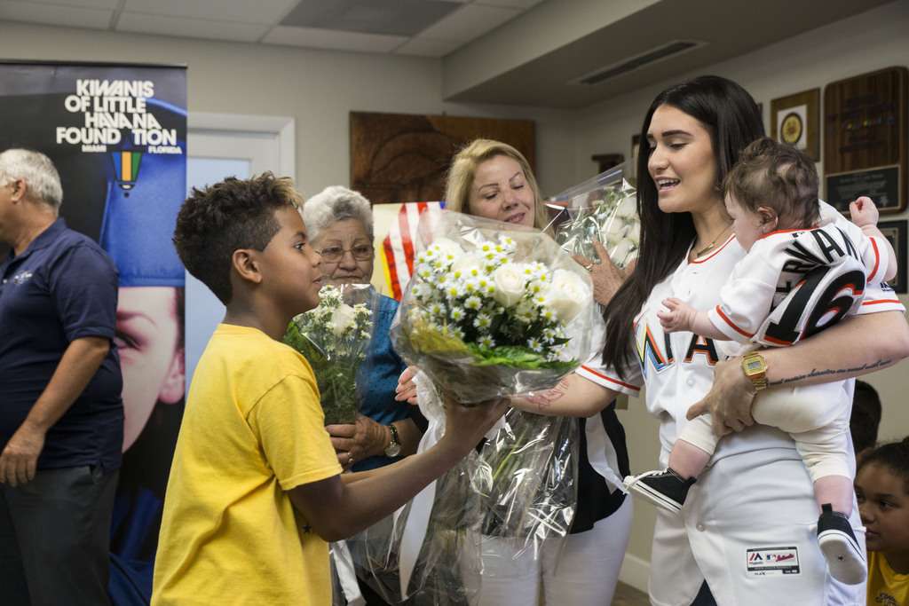 Antoniel Ruiz, 11, gives flowers to Maria Arias in part of the commemoration of José Fernández at Kiwanis of Little Havana in Miami on Monday, July 31...