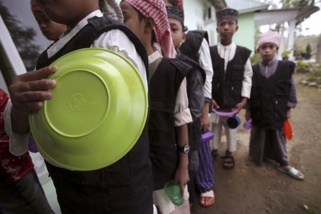 In this July 22, 2017, photo, students line up for lunch at Al Hidayah Islamic Boarding School in Sei Mencirim, North Sumatra, Indonesia. The school w...