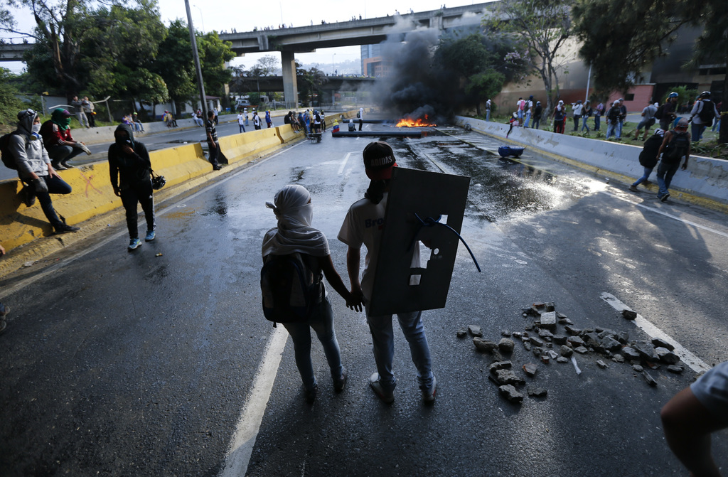 FILE - In this April 24, 2017 file photo, a couple holds hands at a road block set by anti-government protesters in Caracas, Venezuela. Protesters shu...