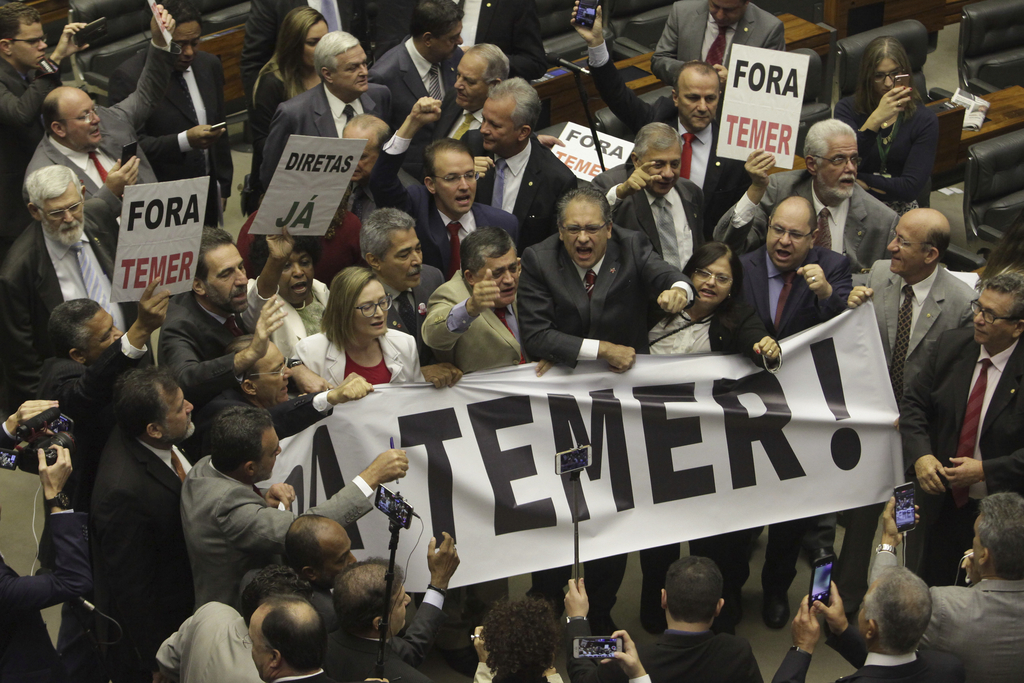 """Opposition lawmakers hold a banner that reads in Portuguese: """"Temer Out!"""" during a congressional before the key vote by Brazil's lower house on whethe..."""