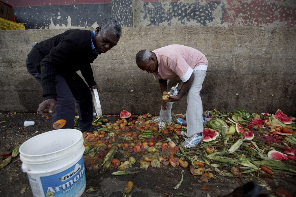 FILE - In this May 31, 2016 file photo, Pedro Hernandez, left, and his friend Luis Daza pick out tomatoes from the trash area of the Coche public mark...