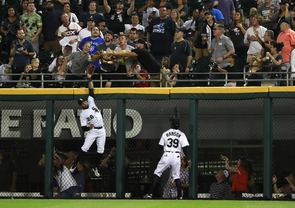 Chicago White Sox center fielder Leury Garcia (28) leaps for a home run by Toronto Blue Jays' Justin Smoak as right fielder Alen Hanson (39) watches d...