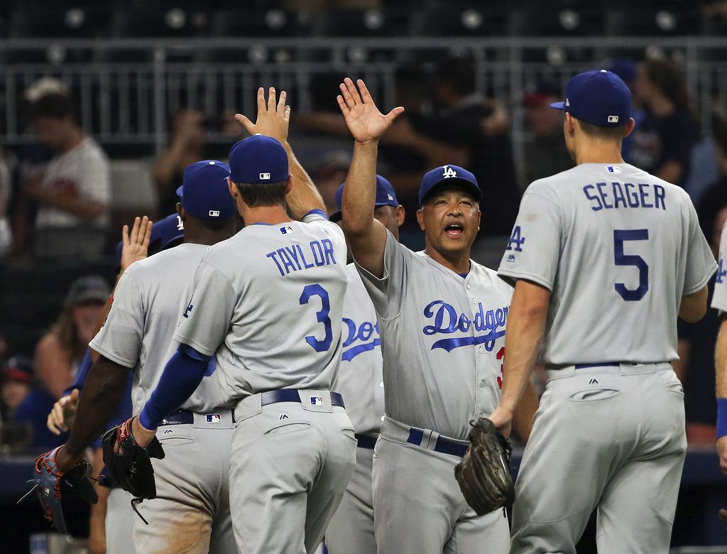 Los Angeles Dodgers manager Dave Roberts (30),center, celebrates with his players after defeating the Atlanta Braves in a baseball game Tuesday, Aug. ...