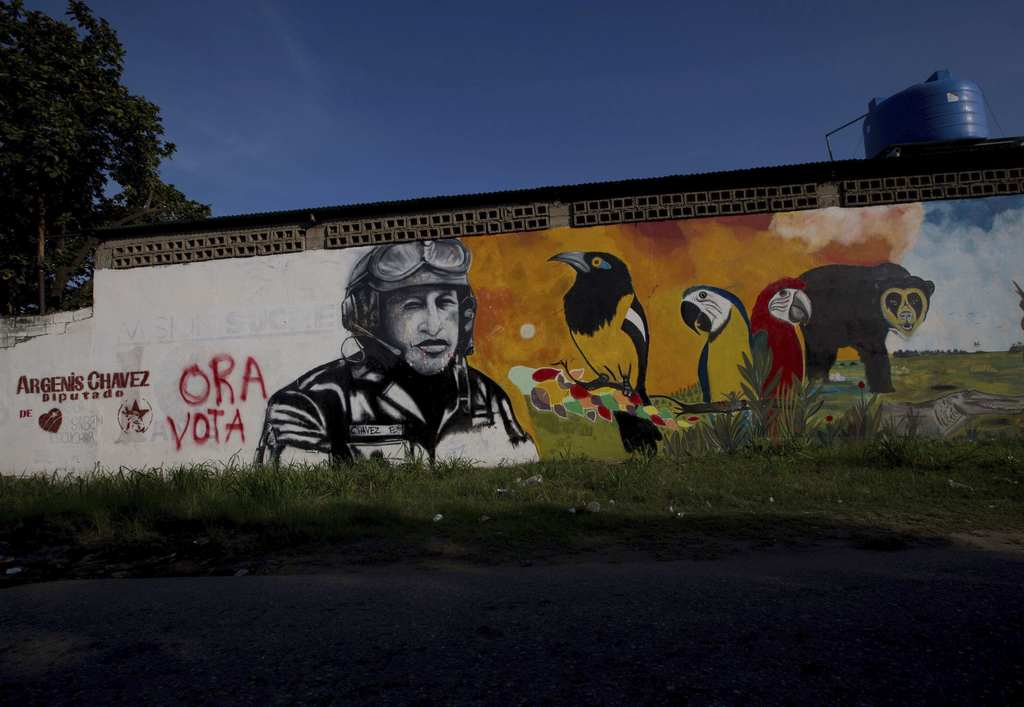 FILE - In this Nov. 23, 2015 file photo, a mural with the image of Venezuela's late President Hugo Chavez shares space with a political ad that urges ...