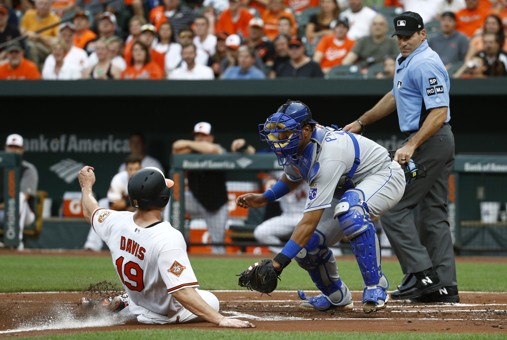 Baltimore Orioles' Chris Davis, left, is tagged out by Kansas City Royals catcher Salvador Perez on a fielder's choice ground ball that was hit by Tim...