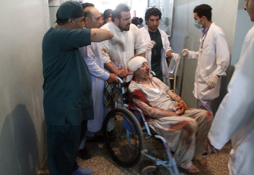 Relatives assist a wounded man in a hospital after a suicide attack on a mosque in Heart, Afghanistan, Tuesday, Aug. 1, 2017. An Afghan hospital offic...