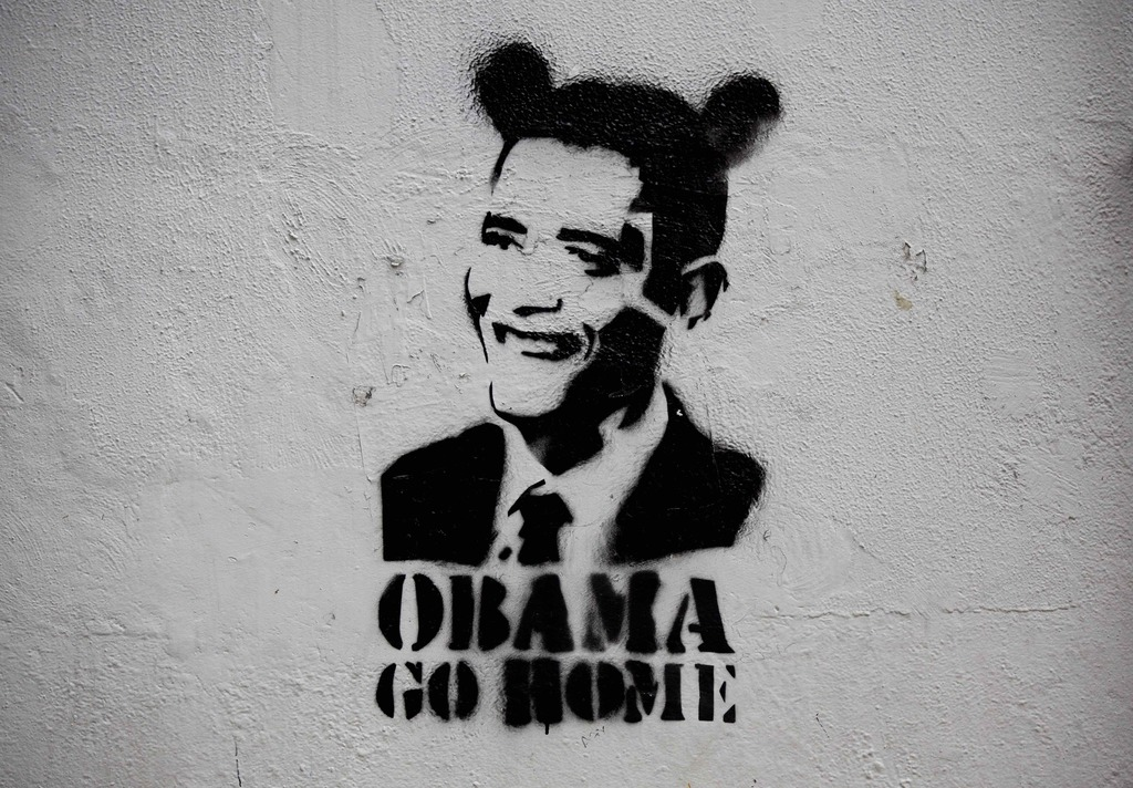 """FILE - This July 21, 2015 file photo shows an image of President Barack Obama wearing fake ears and the slogan """"Obama go home"""" on a street wall in Car..."""
