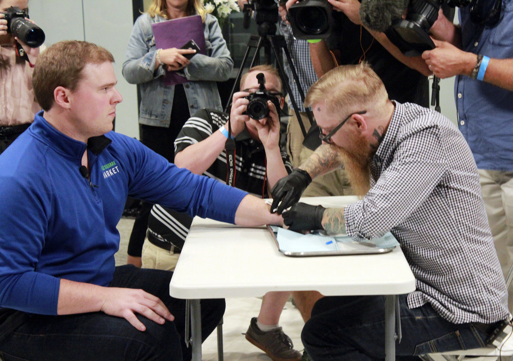 Tony Danna, left, vice president of international development at Three Square Market in River Falls, Wis., receives a microchip in his left hand at co...