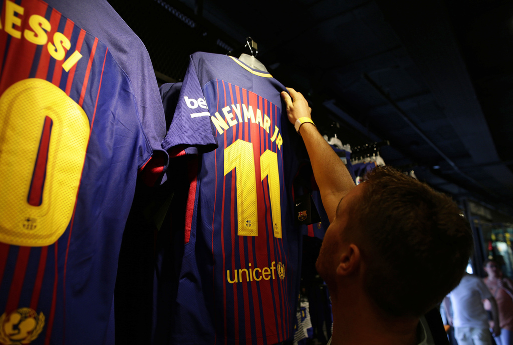 A man holds a FC Barcelona's Neymar t-shirt in a store of the Camp Nou stadium in Barcelona, Spain, Wednesday, Aug. 2, 2017. Neymar has told Barcelona...