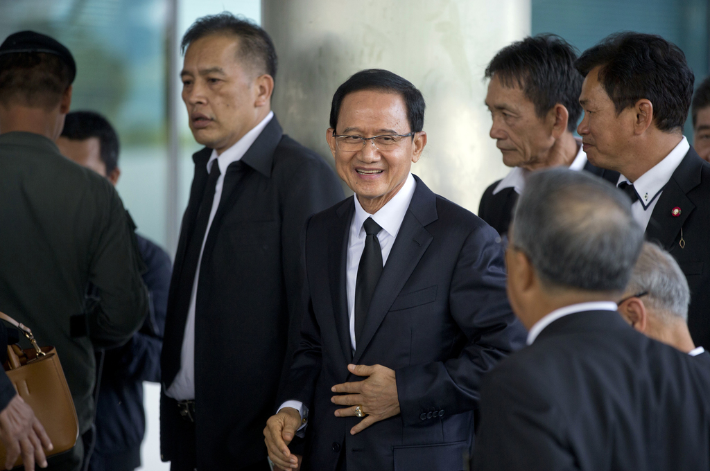 Thailand's former Prime Minister Somchai Wongsawat, center, smilies upon his arrival at a courthouse Wednesday, Aug. 2, 2017, in Bangkok, Thailand. A ...